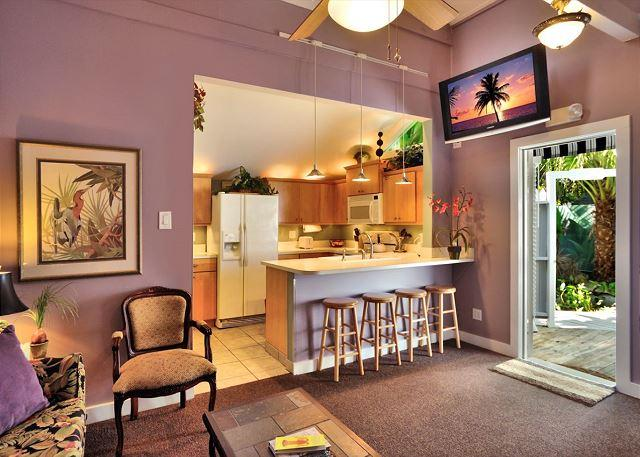 View of Kitchen Past Bar Seating From Stylish Living Room Area. Complete With Flat Screen TV, Ceiling Fan, and Access to the Beautifully Landscaped Outdoors - Sunset Suite - Nightly - Key West - rentals