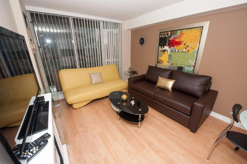 Large Living & Dining room equipped with Plasma LCD TV, Fireplace, Stereo system with Ipod dock - Canada Suites Toronto Furnished Apartments on Bay - Toronto - rentals