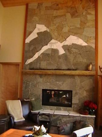Custom stone fireplace with large seating area on hearth. - Three Bears Chalet - Sun Peaks - rentals