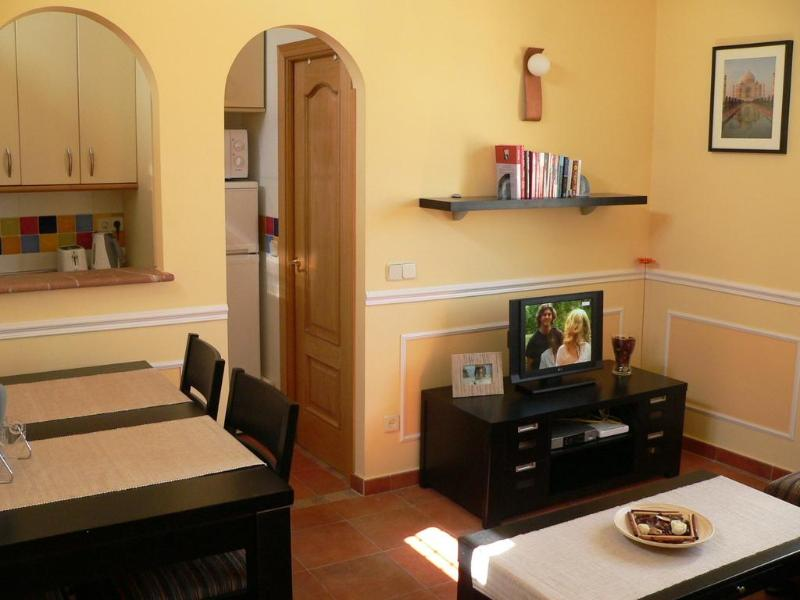 Living room with dining table for 4, coffee table, flat screen TV on TV cabinet - Beautiful 1 bed apartment 10 mins walk from Sol - Madrid - rentals