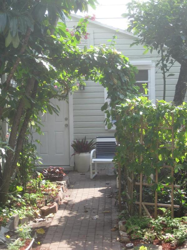 "A brick walk leads through a gated garden to the front door - ""Old Florida"" Garden Cottage With Shared Pool - West Palm Beach - rentals"