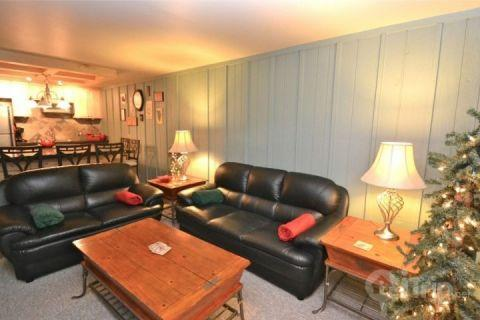 After a day of skiing, relax on the overstuffed leather furniture in the roomy living area with a large-screen TV, or gather for a game of cards. - Snow Country in Old Town - Park City - rentals