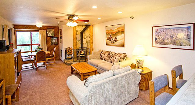 The Living Area has an LED tv, Wood Burning Fireplace, and Dining Table Toward View - Aspen Creek 208 - Mammoth Condo - Near Ski Lift - Mammoth Lakes - rentals