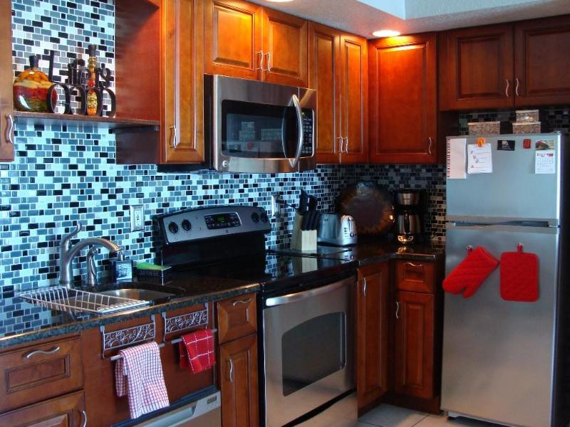 All New Kitchen - Cherry Cabinets, Granite Counters and Stainless Steel Appliances - Oceanfront Luxury Condo with Double Balcony - New Smyrna Beach - rentals