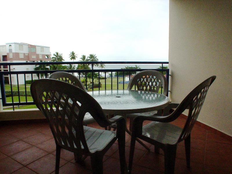Balcony seating area with beautiful beach and garden view. - Haciendas del Club Golf & Playa IV307 - Cabo Rojo - rentals