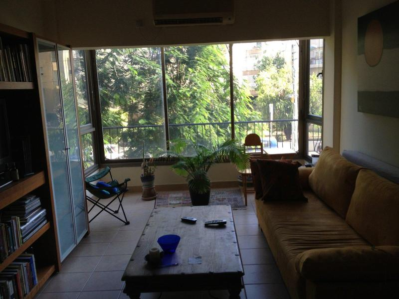 The living room looking toward the quiet Shimon Hatrsi Street and this beautiful tree - Charming apt. sea/fun/park N. TLV - Tel Aviv - rentals