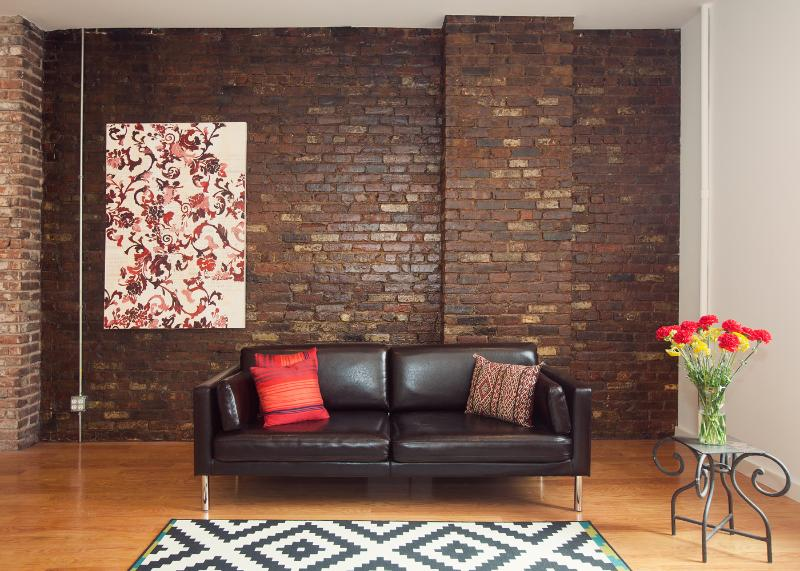 Exposed brick wall, original artwork, modern sofa in the living room - Luxury 2 Bdrm Artist Loft- 5 mins to Times Squ - Queens - rentals