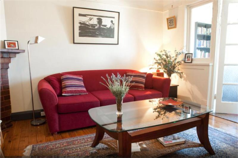 Lounge room with sofabed and a small study to the right - Light & spacious art-deco apartment, city views - Petersham - rentals
