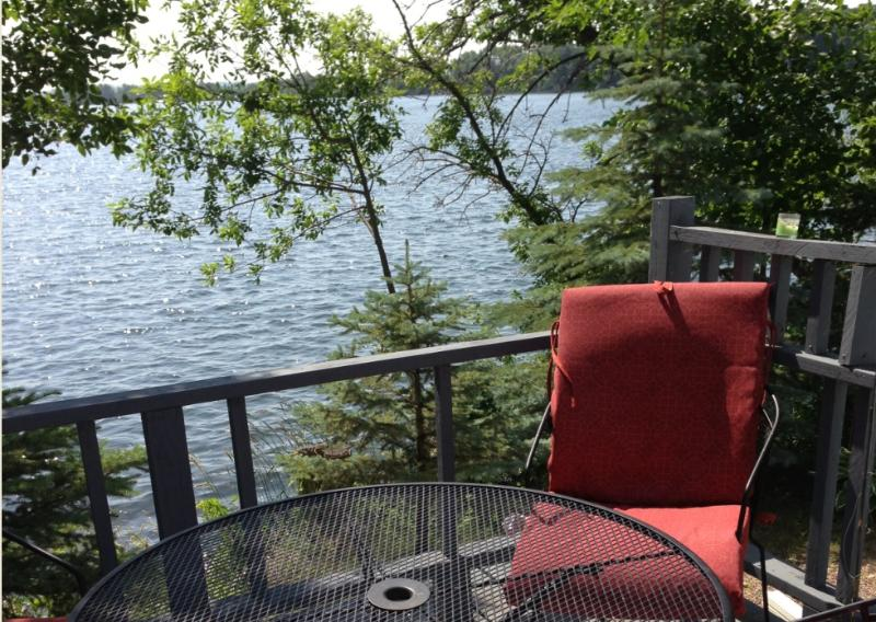 Enjoy the morning sun on the deck that is just a few feet from Lower Elk Lake. - Family Home on 2 Lakes! 335' of Lakeshore. Pontoon - Hoffman - rentals