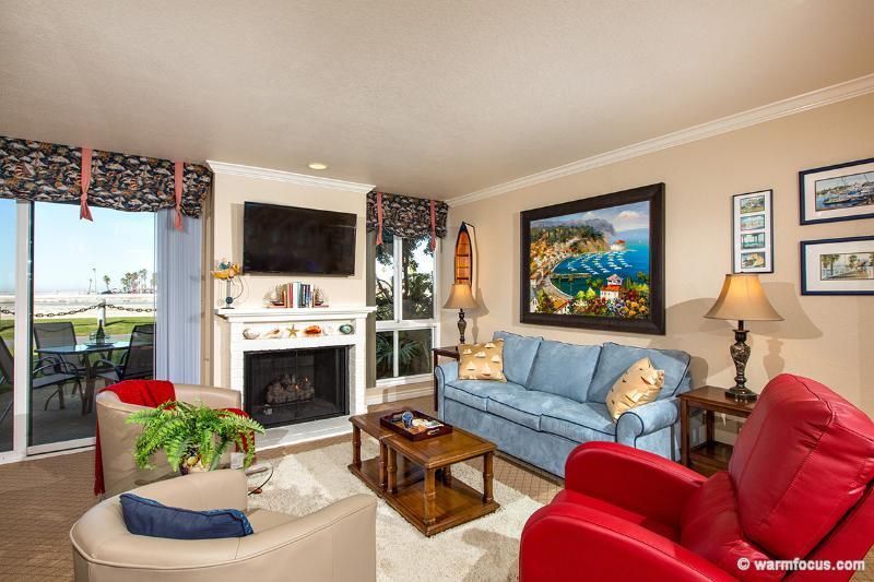 This cozy living area is your window to the ocean, sand, and harbor! - Seaside Cottage~Walk Out to Your Patio and Yard! - Oceanside - rentals