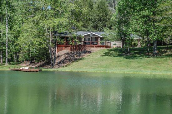 VIEW OF THE CABIN FROM THE LAKE - ALONE AT LAST~2 BEDROOM~1 BATH~SLEEPS 4~PRIVATE LAKE~CREEK~HOT TUB~OUTDOOR FIREPLACE~GAS LOGS~GAS GRILL~WIFI~SECLUDED~$125 A NIGHT!!! - Blue Ridge - rentals