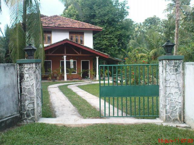 Front view with concrete road, entrance and gate  - Holiday cottage bordering river with birds & trees - Kurunegala - rentals