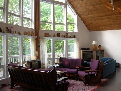 Living room feat: vaulted ceilings, wood fireplace, full height windows, deck access & extraseating. - Lakefront Muskoka Cottage - SuckerLakeCottage.com - Ontario - rentals