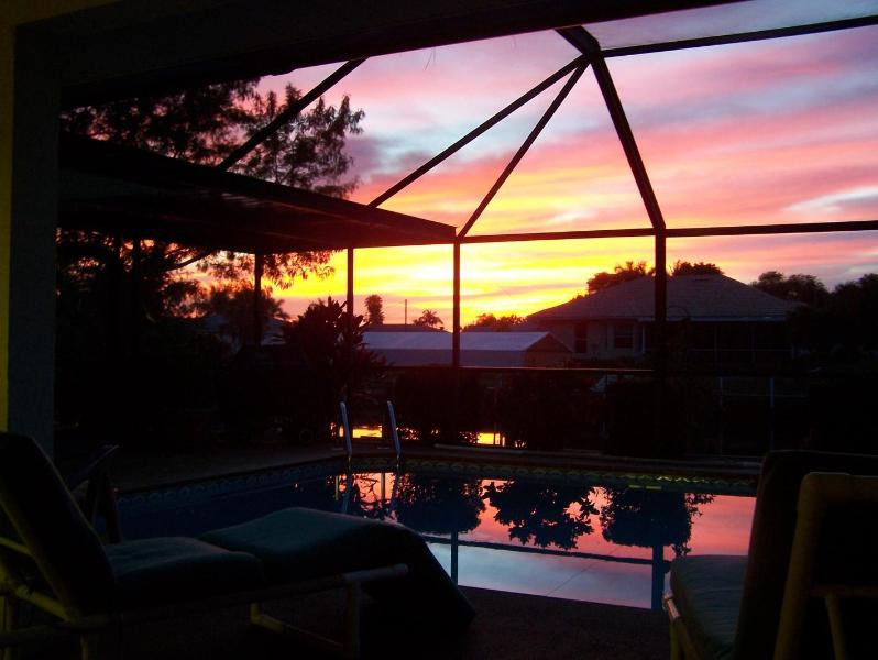 Sunset thru the lanai with reflection off the pool - Beautiful 3BR/2BA Gulf Access Home Heated Pool&Spa - Cape Coral - rentals