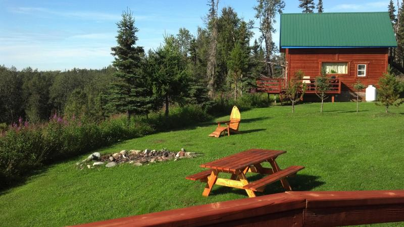 Cabin sits on bluff facing river with firepit in foreground - River Vacation Cabin in Kenai Peninsula, ALASKA - Kenai - rentals