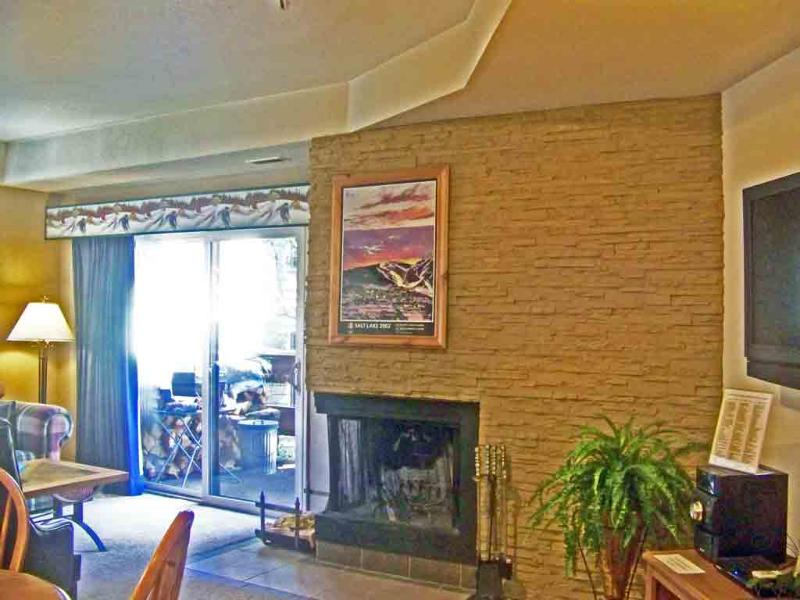 Livingroom / wood burning fireplase set in stacked rock wall & glass door to deck / view of mountain - Lift Line 207 Walk to PCMR - Many Sundance Venues - Park City - rentals