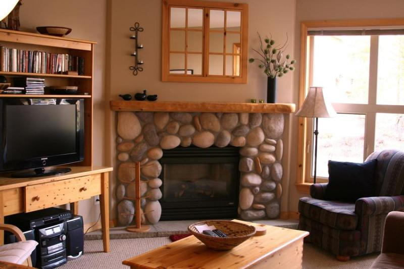Living Room with a rock fireplace and a 32