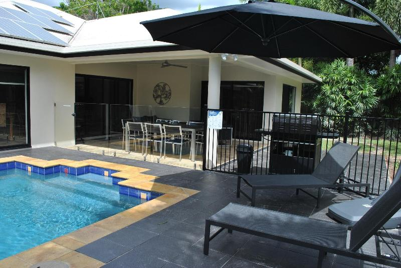 Poolside patio with couch & armchair seating, alfresco dining, BBQ & loungers - Villa Blue - luxury tropical retreat in Palm Cove - Palm Cove - rentals