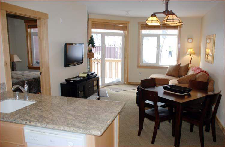 Living Room from Kitchen (Notice Skier skiing back to condo) - SUNSTONE LODGE Luxury Slopeside 2 bedroom 2 Bath - Mammoth Lakes - rentals