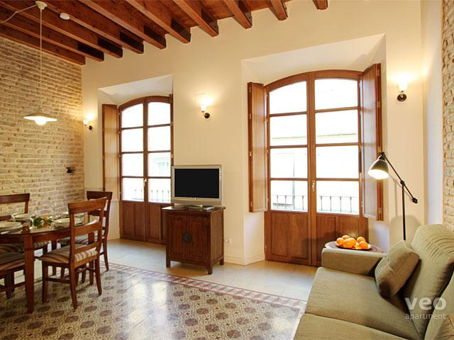 Bright living room featuring exposed brick walls, beams and original floor tiles. - Relator. Authentic 1-bedroom - Seville - rentals