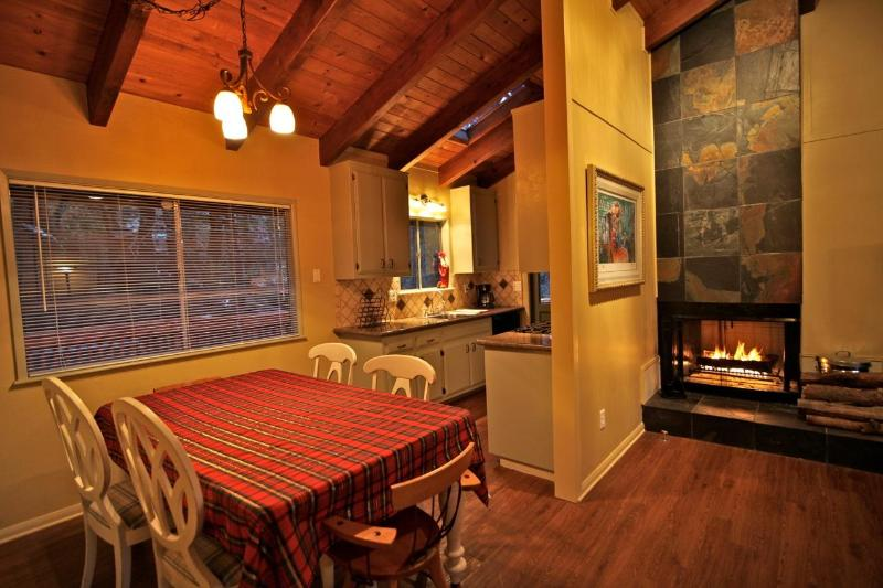 Dining table with kitchen and wood burning fireplace in the background - Blue Jay Retreat - Lake Arrowhead Rustic Luxury - Lake Arrowhead - rentals