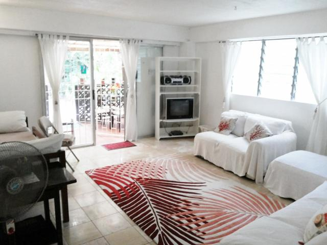 Living Room with Single Bed - Quaint EcoFriendly Red Coral Apartment at the Chi - Bridgetown - rentals
