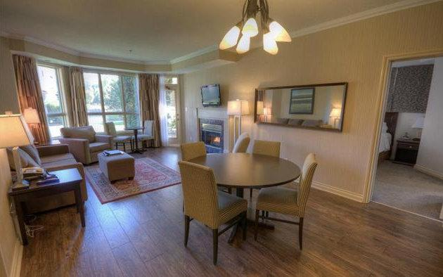 Spacious living dining room with fireplace, TV and access to water front deck. - Waterfront Condo in Delta Grand Okanagan Resort - Kelowna - rentals