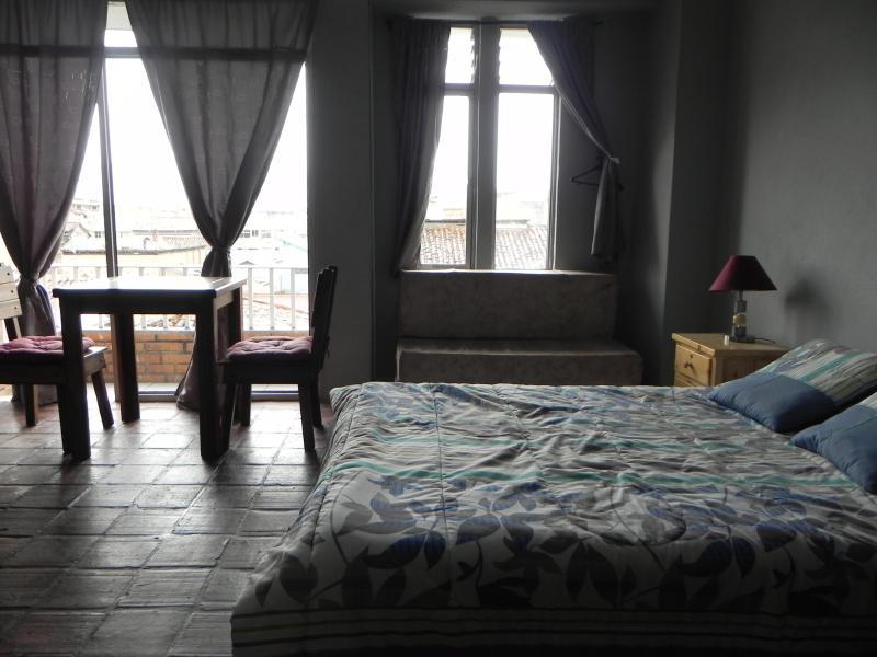 dormitorio con cama de 2 plazas, al fondo esta el balcon de donde se ve parte de la ciudad - Miniapartment Amoblado (Cuenca) - Cuenca - rentals