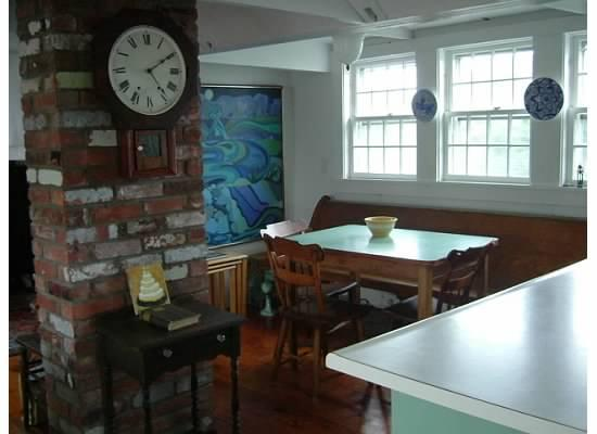 Dining area, windows look out at Commercial St and the bay - Historic Artist Loft, Water Views - Provincetown - rentals