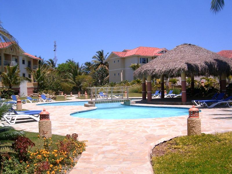 Luscious garden with lawn chairs, umbrellas, barbecue, large pool and gazebo! - Fantastic Condo right on beautiful Cabarete Bay! - Cabarete - rentals