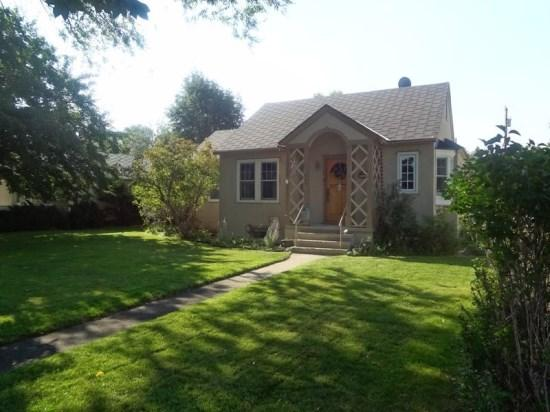 Front view with manicured lawn and large shade trees. - Canyon Cottage - Cody - rentals