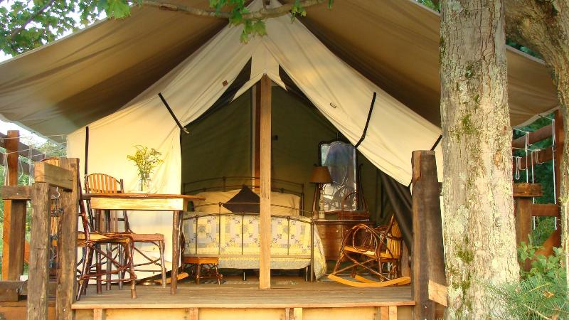 A well-appointed bedroom and a covered deck are waiting for your comfort and relaxation. - Glamping at Campbell Farm -Private -Mountain Views - Fort Hill - rentals