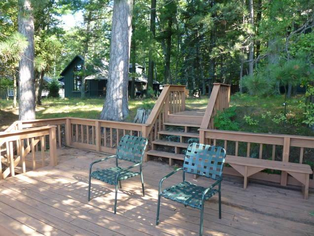 View of the private deck, which overlooks the lake, back to the cottage. - Higgins Lakefront Cottage & dock, in Deep Woods - Higgins Lake - rentals