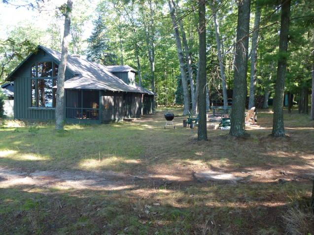 View from the entance to the deck, towards the cottage in a clearing, among tall trees. - Higgins Lakefront Cottage & dock, in Deep Woods - Higgins Lake - rentals