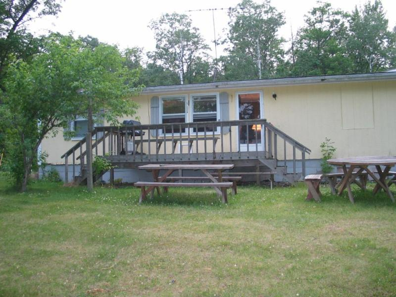 Front of home, with deck and picnic tables facing lake - Lake home on great fishing and swimming lake - Mora - rentals
