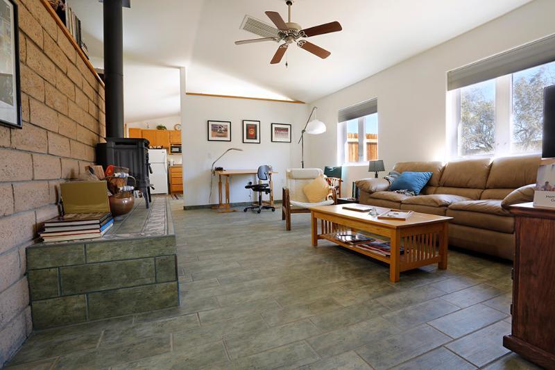 The living room - artist's table on back wall, wood burning stove on left. - 1200sq ft Romantic Getaway, Walk to Hiking & Rocks - Joshua Tree - rentals