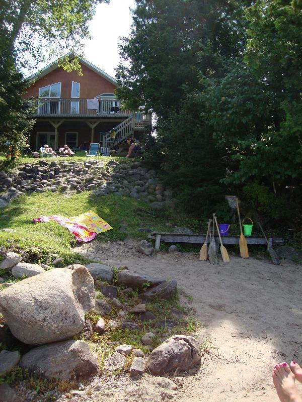 Picture is from the beach in front of the house, it overlooks the beach area and the fire pit area up at the house deck. - Executive lakefront home- MUSKOKA - Restoule - rentals