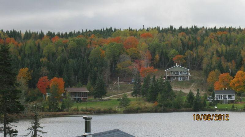 Log house on left from across the lake in fall - Lake front Log Home ( year round vacation rental ) - Bonaventure - rentals