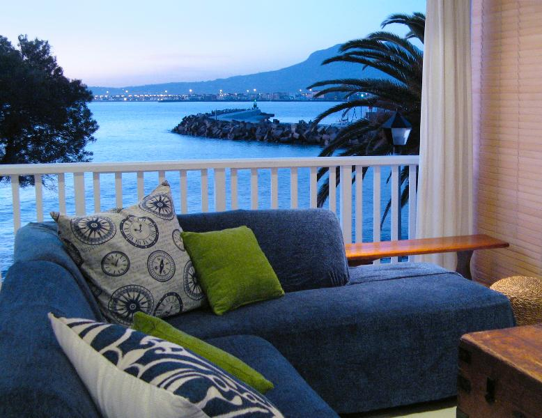 Evening view of False Bay and harbour, huge fold back ddors to experience the ocean in youre lounge - Bikini Beach Self Catering Suites - Gordon's Bay - rentals