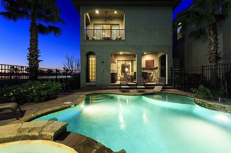A beautiful lit pool creates an enchanting nighttime scene - Signature Villa | Elegant 5 Bed Villa with Golf & Lake Views featuring a South Facing Pool, Outdoor Summer Kitchen, & Games Room - Kissimmee - rentals