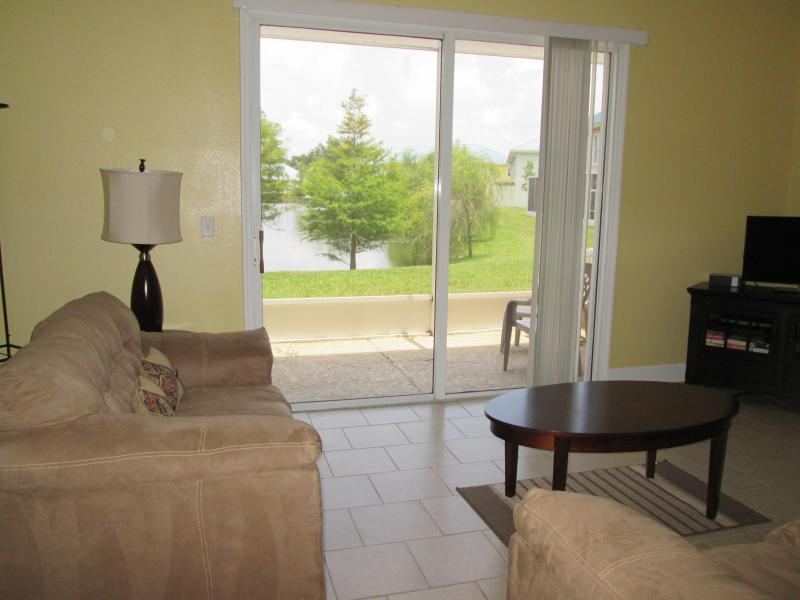 Living Room & Patio with a view of the pond & pool! - Kissimmee Townhome - Beautiful Pond & Pool View! - Kissimmee - rentals