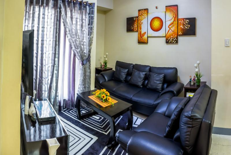 Cozy and comfy living room with a 46 inch TV, a leather sofa, nice carpet, and decorations - 3-BR, CONDO EDSA GRAND Residences - Quezon City - rentals