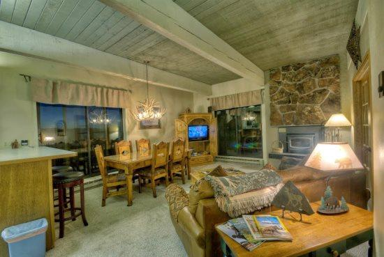 Living and Dining Area with Deck Access Doors, Wood Burning Fireplace, TV, Sleeper Sofa - Storm Meadows C310 - Steamboat Springs - rentals