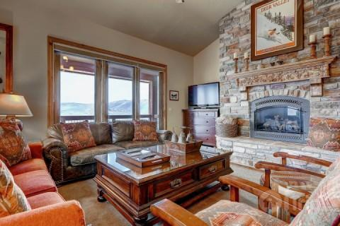 Grand living / family room with flatscreen HDTV, floor to ceiling oversized windows to allow natural light, private balcony and stone fireplace. - Bella Shores - Heber City - rentals