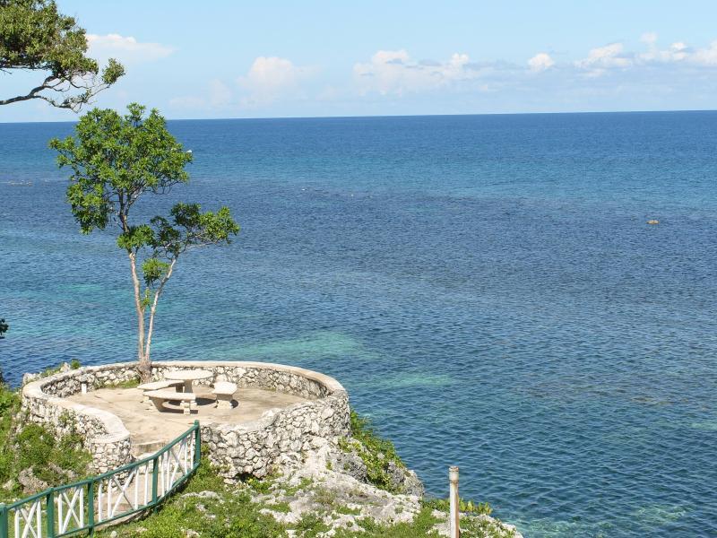 View to the left of your private balcony, seating area on edge of a cliff - carib apartments mahogany beach ocho rios - Ocho Rios - rentals