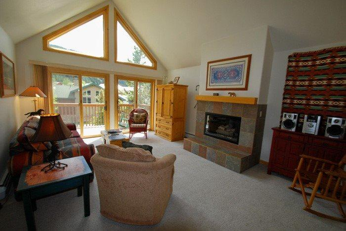 Open living room with plenty of natural light and a stone fireplace - Snake River Village 05 - Walk to slopes, ski area views, washer/dryer, private garage! - Keystone - rentals