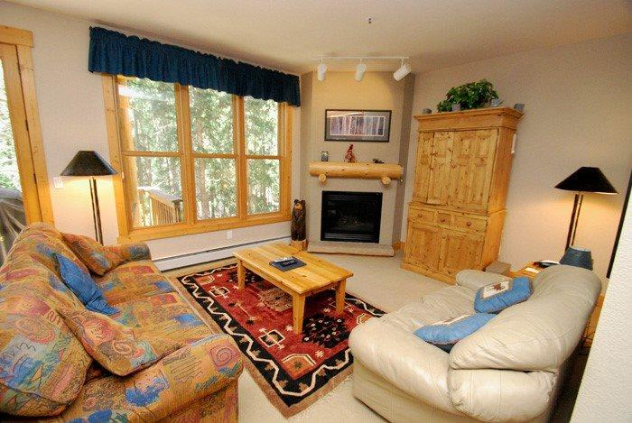 Comfortable living room with a fireplace and an outdoor patio - Trappers Crossing 8763 - Washer/dryer, jetted tub, on shuttle route, outdoor hot tub on site! - Keystone - rentals