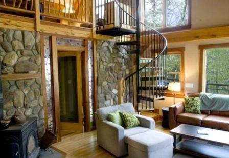 Upscale Living Room with a Cast Iron Fireplace, Leather Sofa, and Hardwood Floors - Laurel Branch - Less than 15 Minutes from Boating and Fishing on Fontana Lake This Custom Built Rental Is Secluded by Trees and Has a Hot Tub, Easy Access, and Foosball Table - Bryson City - rentals