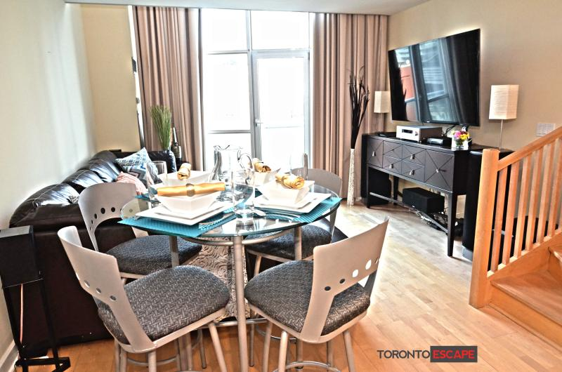 Open Concept living and dining area with 60inch television and L shaped sofa bed - Luxury SoHo Loft - Heart of Entertainment District - Toronto - rentals