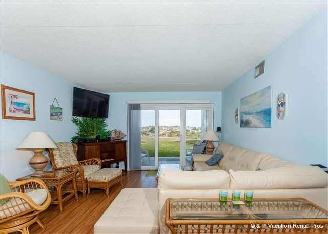 Our open-plan condo includes a comfy sectional and wood floor. - Tradewinds 201 - Ground Floor Unit, pool, tennis, beach - Saint Augustine - rentals